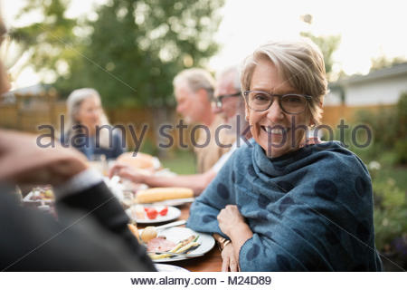 Portrait smiling senior woman enjoying garden party lunch at patio table - Stock Photo
