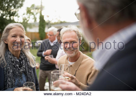 Smiling senior friends talking, drinking wine at party on patio - Stock Photo
