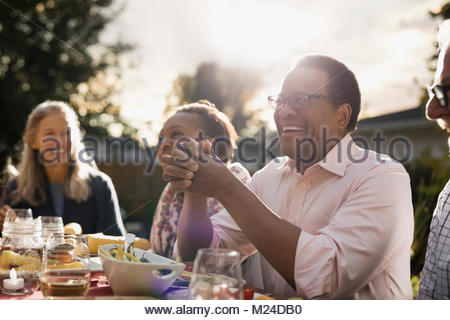 Laughing senior man enjoying garden party lunch with friends at sunny patio table - Stock Photo