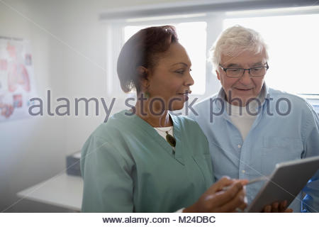 Female doctor with digital tablet talking to senior male patient in examination room - Stock Photo