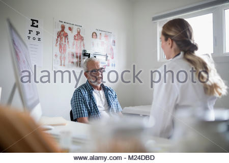 Female doctor talking with senior male patient in examination room - Stock Photo