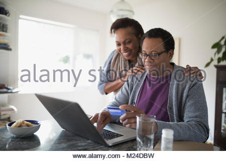 Smiling senior couple with credit card paying bills online at laptop in kitchen - Stock Photo