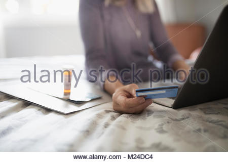 Woman with credit card reordering prescription medication at laptop on bed - Stock Photo