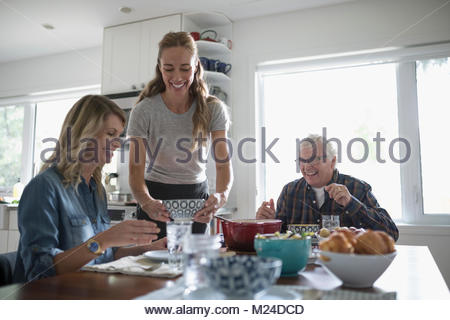 Smiling daughters and senior father eating at kitchen table - Stock Photo