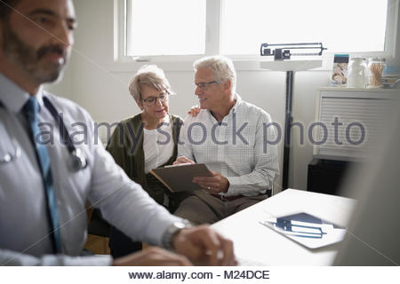 Senior couple patient filling out paperwork on clipboard in doctor - Stock Photo