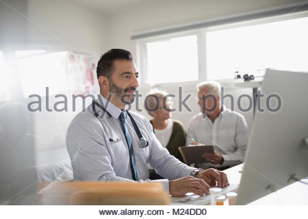 Male doctor working at laptop with senior couple patient in background in doctor - Stock Photo