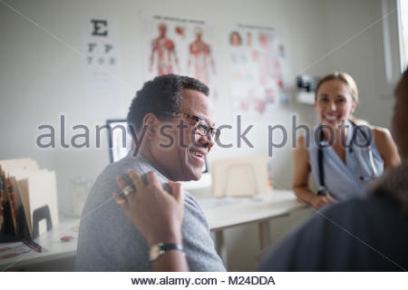 Smiling senior man talking with wife and doctor in examination room - Stock Photo