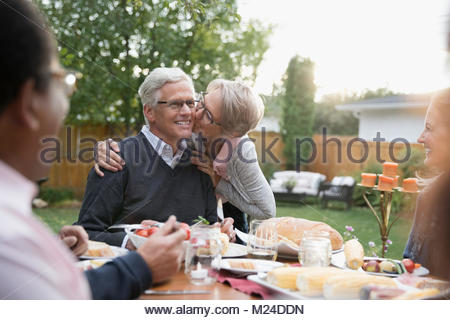 Affectionate senior wife kissing husband on cheek at garden party lunch patio table - Stock Photo