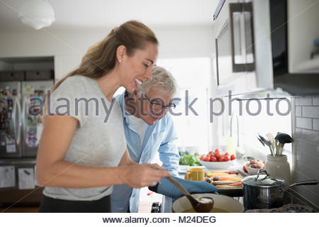 Smiling daughter and senior father cooking at stove in kitchen - Stock Photo