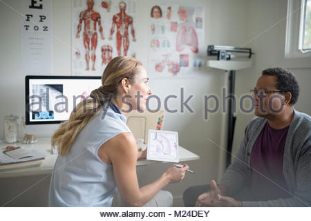 Female doctor with digital tablet talking with senior male patient in examination room - Stock Photo