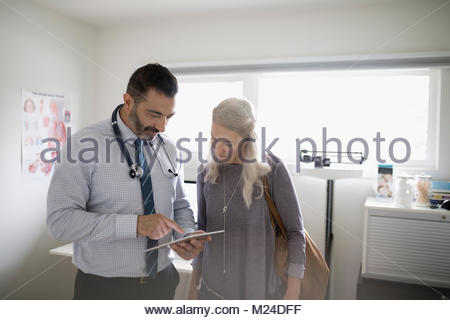 Male patient with digital tablet talking to senior female patient in examination room - Stock Photo