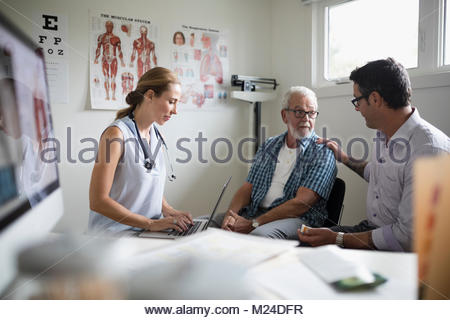 Son comforting senior father in examination room with female doctor using laptop - Stock Photo