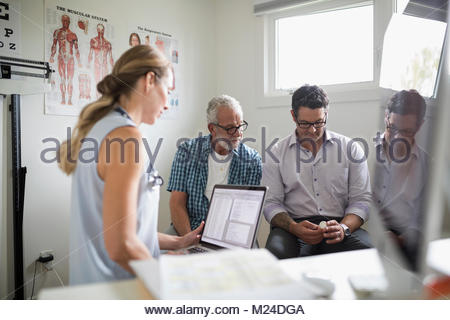Female doctor with laptop and senior male patient and son examining prescription medication in examination room - Stock Photo