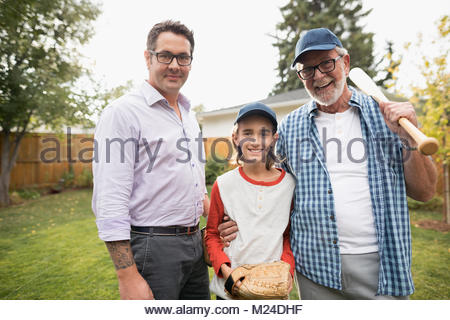 Portrait smiling multi-generation family men playing baseball in backyard - Stock Photo