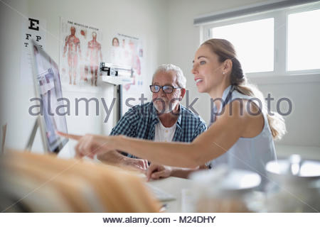 Female doctor showing computer to senior male patient in examination room - Stock Photo