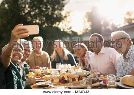 Smiling senior friends posing for selfie at garden party lunch at sunny patio table - Stock Photo