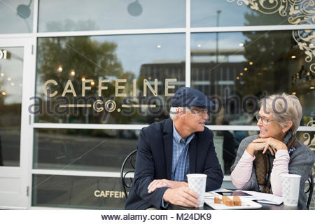 Senior couple drinking coffee and talking at sidewalk cafe - Stock Photo