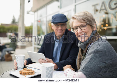 Portrait smiling, confident senior couple using digital tablet and drinking coffee at sidewalk cafe - Stock Photo