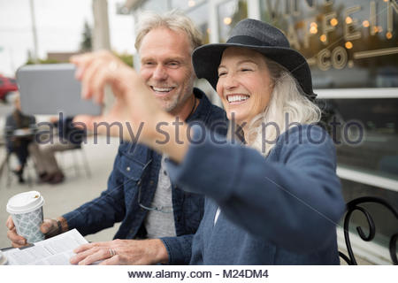 Smiling senior couple taking selfie with camera phone at sidewalk cafe - Stock Photo