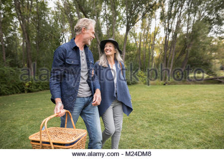 Smiling senior couple walking, carrying picnic basket in park - Stock Photo