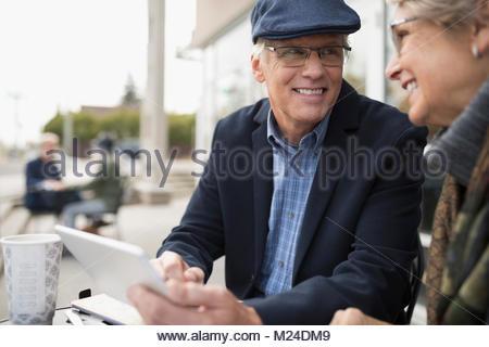 Smiling senior couple using digital tablet at sidewalk cafe - Stock Photo