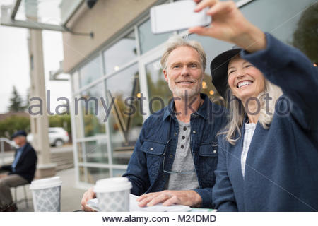 Smiling senior couple taking selfie with camera phone at sidewalk cafe - Stock Photo