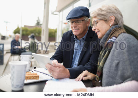 Senior couple using digital tablet at sidewalk cafe - Stock Photo
