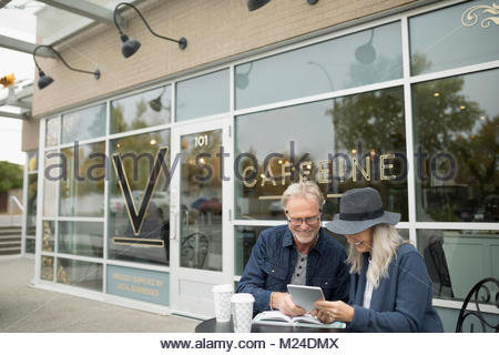 Smiling senior couple drinking coffee and using digital tablet at sidewalk cafe - Stock Photo