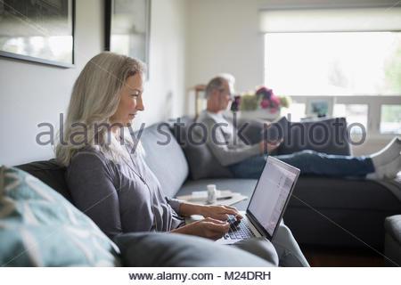 Senior woman using laptop on living room sofa - Stock Photo