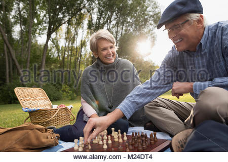 Senior couple playing chess in park - Stock Photo