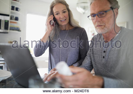 Senior couple reordering prescription medication at laptop, talking on cell phone - Stock Photo