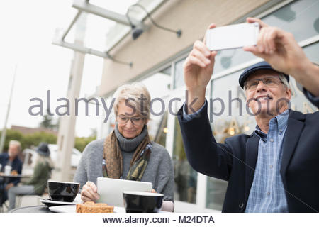 Senior couple using digital tablet and camera phone, drinking coffee at sidewalk cafe - Stock Photo