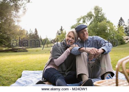 Portrait smiling, affectionate senior couple enjoying picnic in park - Stock Photo
