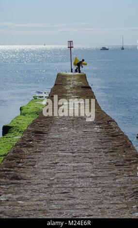 Boy Crabbing from a Coastal Stone Pier Breakwater at Dawlish Beach. Summer 2015 on a Tranquil Day. Devon, UK. - Stock Photo