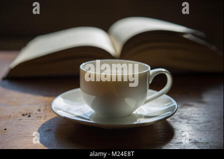 cup of coffee on the background of an open book. A cup on the table in the room. - Stock Photo