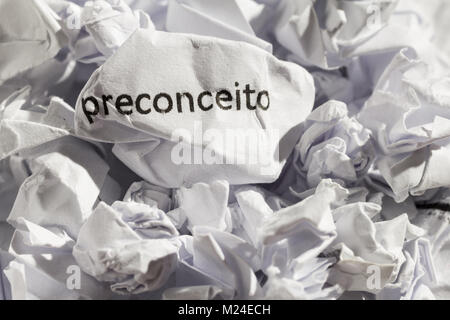 Crumpled paper written preconceito, portuguese word for prejudice. Illustrative concept of ideology thrown into - Stock Photo