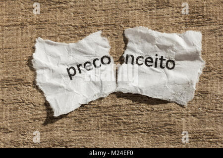 Torn paper written preconceito, portuguese word for prejudice, over wooden background. Old and abandoned idea or - Stock Photo