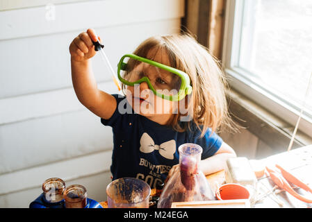 A 3-year old toddler girl works with science experiment equipment - Stock Photo