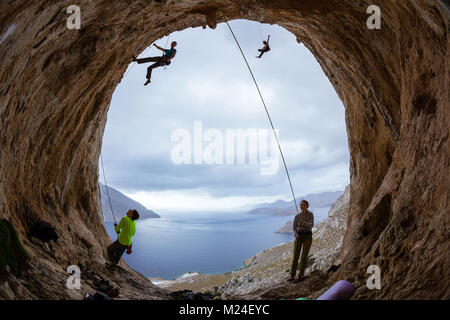 Rock climbers in cave: belayers watching leading climbers, two climbers swinging on ropes or being lowered down - Stock Photo