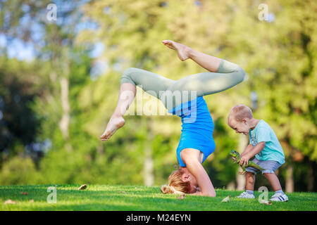 Young woman working out outdoors, standing on head, little son playing beside her - Stock Photo