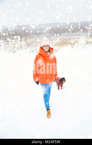 Full length shot of a happy woman walking her small dog outdoor in winter. - Stock Photo