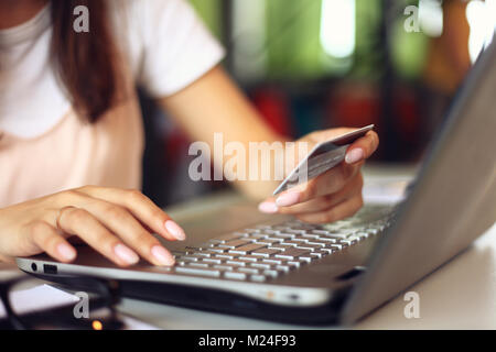 Young woman holding credit card and using laptop computer. Online shopping concept. - Stock Photo
