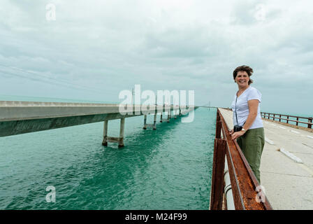 a mature woman standing on the old bridge between the Florida Keys - Stock Photo