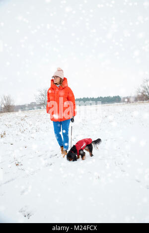 Full length shot of happy woman walking with her small dog outdoor in the snowfall. - Stock Photo