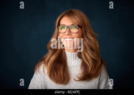 Close-up portrait of beautiful mature woman looking up and smiling confidently while standing at dark background. - Stock Photo