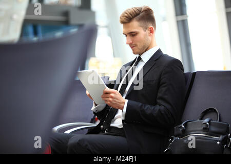 Businessman Using Digital Tablet In Airport Departure Lounge - Stock Photo