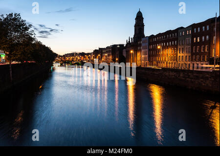 Dublin City at sunset with view over the river Liffey and historical Grattan bridge in the distance. Long exposure. - Stock Photo