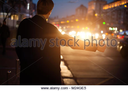 The guy stops a taxi at night. Man stops hitchhiking. - Stock Photo