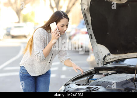 Worried driver with car breakdown calling insurance on the street - Stock Photo