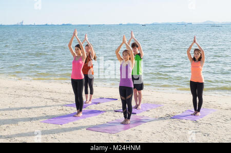 Yoga class at sea beach in evening ,Group of people doing namaste poses with clam relax emotion at beach,Meditation - Stock Photo